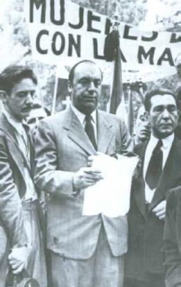 """Pablo Neruda. En ese momento cA?nsul de Chile en MAi??xico, lee su """"Dura elegAi??a"""" dedicada a la 'Madre herA?ica'. A su izq. el lAi??der sindical chileno Salvador Ocampo"""