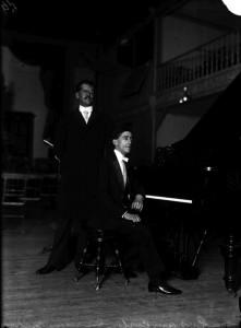 Carlos J. Meneses junto a un piano antes de un concierto, ca. 1914, inv. 21656. SECRETARÍA DE CULTURA. - INAH. - FOTOTECA NACIONAL. - MÉX. Reproducción autorizada por el INAH.