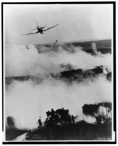 Two bombs tumble from a Vietnamese Air Force A - 1E Skyraider over a burning [Viet] Cong hideout near Cantho, South Viet Nam, 1967. Library of Congress, EUA.